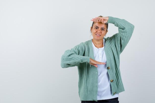 Молодая женщина показывает весы в белой футболке и мятно-зеленом кардигане и выглядит счастливой