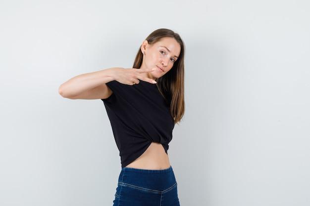 Giovane donna che mostra il gesto delle forbici in camicetta nera e guardando concentrato
