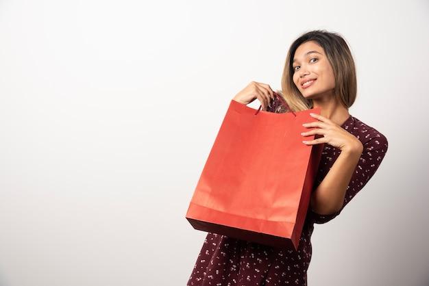 흰 벽에 쇼핑백을 보여주는 젊은 여자.