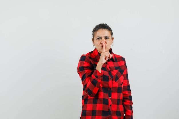 チェックシャツで沈黙のジェスチャーを示し、注意深く見ている若い女性、正面図。