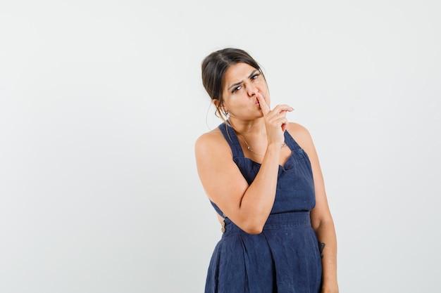 ドレスを着て沈黙のジェスチャーを示し、注意深く見ている若い女性