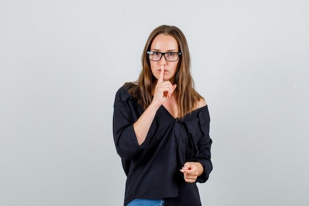 シャツ、ショートパンツ、メガネで沈黙のジェスチャーを示し、注意深く見ている若い女性。正面図。