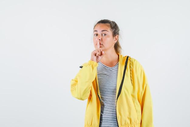 Молодая женщина показывает жест молчания в футболке, куртке и смотрит осторожно. передний план.