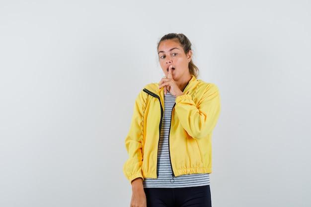 Tシャツ、ジャケットで沈黙のジェスチャーを示し、賢明に見える若い女性。正面図。