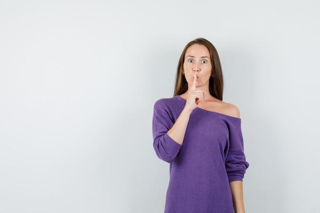 紫のシャツで沈黙のジェスチャーを示し、注意深く見ている若い女性、正面図。