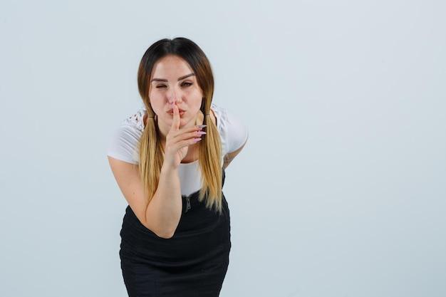 Giovane donna che mostra gesto di silenzio e sembra seria
