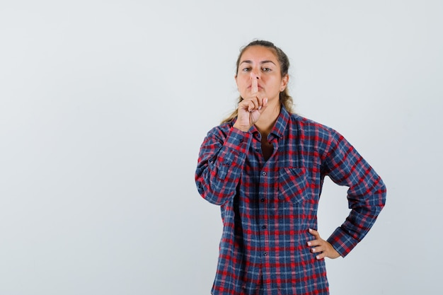 Молодая женщина показывает жест молчания, держа руку на талии в клетчатой рубашке и выглядит серьезной