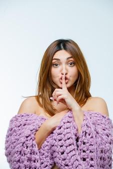 沈黙のジェスチャーを示す若い女性