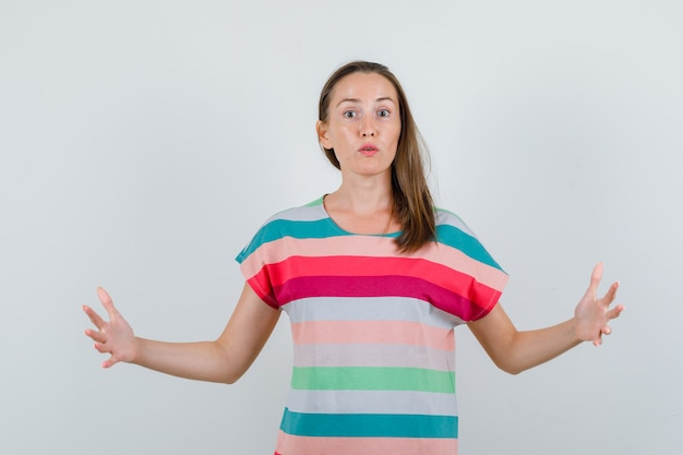 Tシャツでサイズサインを示し、困惑しているように見える若い女性、正面図。