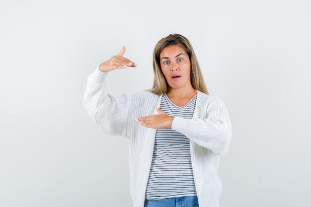 Молодая женщина показывает знак размера в футболке, куртке и выглядит удивленным. передний план.