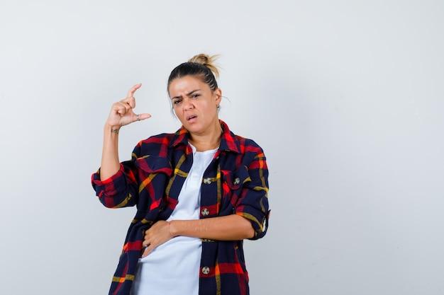 市松模様のシャツで小さいサイズを示し、不機嫌そうに見える若い女性、正面図。