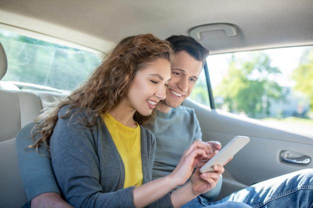 Молодая женщина показывает экран смартфона человеку
