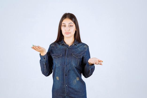 彼女の開いた手で何かを示す若い女性