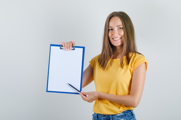 Молодая женщина показывает что-то в буфере обмена в футболке, шортах и выглядит весело
