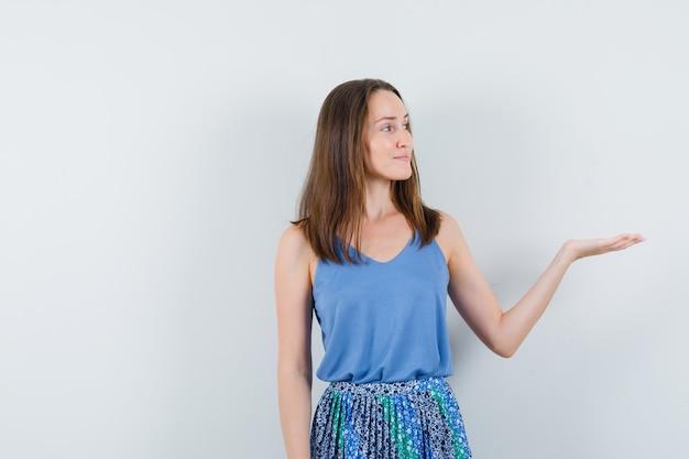 Giovane donna che mostra qualcosa o dà il benvenuto in canottiera, gonna e sembra sicura di sé, vista frontale.