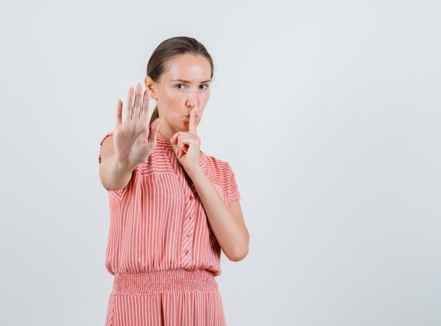 Молодая женщина показывает знаки остановки и молчания в полосатом платье, вид спереди.