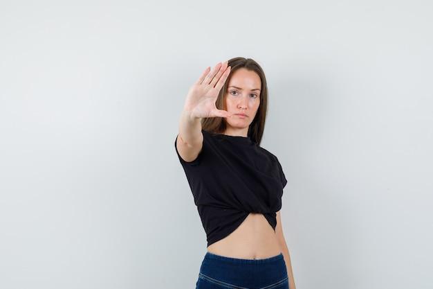 Giovane donna che mostra il gesto di arresto in camicetta nera e che sembra seria