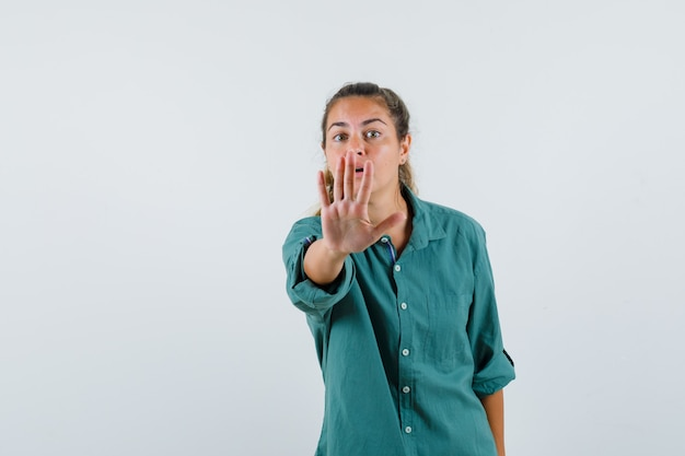 Young woman showing stop gesture in blue shirt and looking troubled