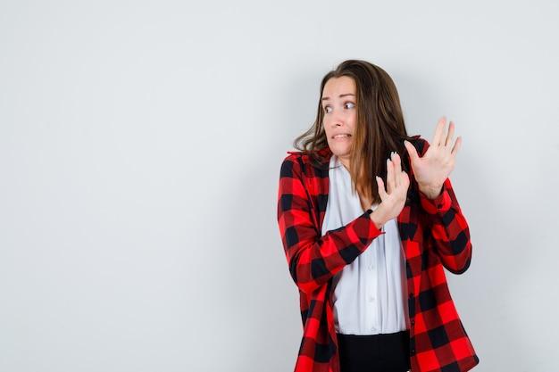 Giovane donna che mostra il gesto di arresto in abiti casual e sembra spaventata, vista frontale.