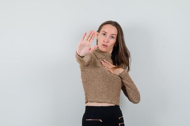 Giovane donna che mostra il gesto di arresto in camicetta dorata e che sembra seria