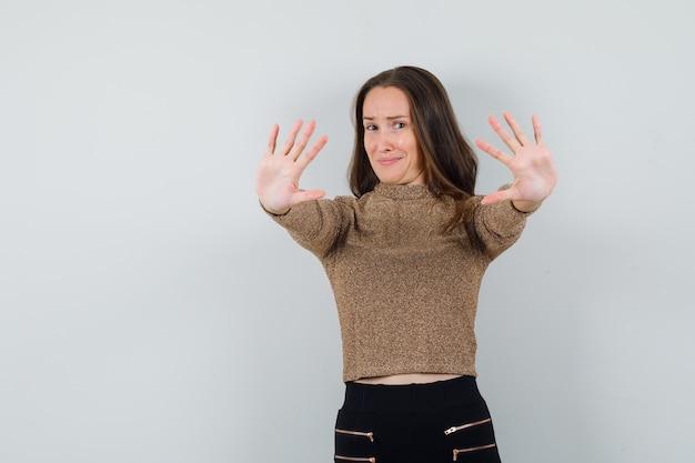 Giovane donna che mostra il gesto di arresto in camicetta dorata