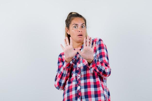 Молодая женщина показывает жест остановки в повседневной рубашке и выглядит испуганной, вид спереди.