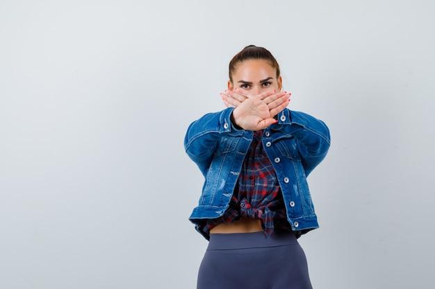 市松模様のシャツ、ジーンズのジャケットで停止ジェスチャーを示し、真剣に見える若い女性、正面図。