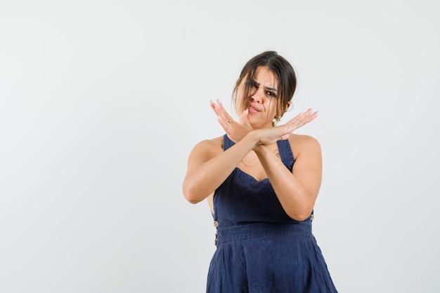 Молодая женщина показывает жест стоп в платье и выглядит раздраженной