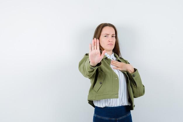Молодая женщина показывает жест остановки в рубашке, куртке и выглядит решительным, вид спереди.