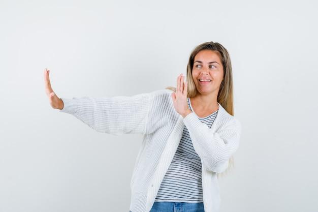 Молодая женщина показывает жест остановки в футболке, куртке и выглядит счастливым, вид спереди.