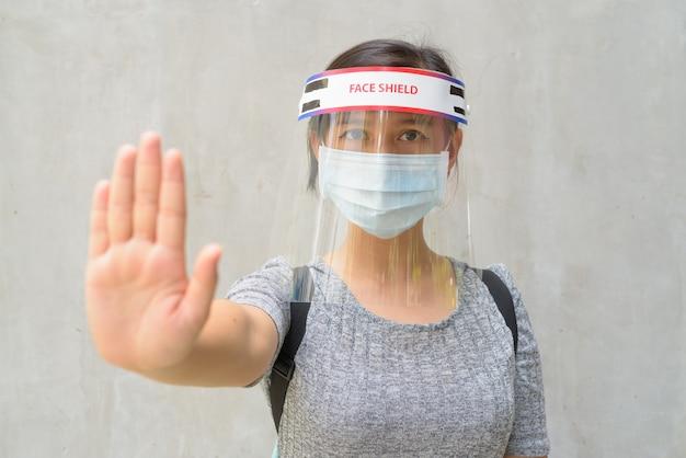 Молодая женщина показывает жест стоп с маской и защитной маской для защиты от вспышки вируса короны на открытом воздухе