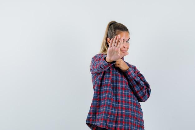 Giovane donna che mostra il fanale di arresto in camicia controllata e che sembra felice