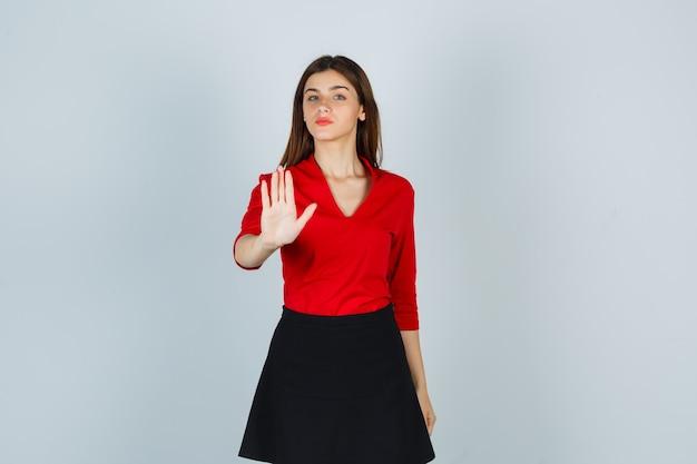 Молодая женщина показывает знак остановки в красной блузке, черной юбке и выглядит серьезно