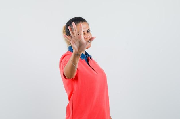 Молодая женщина показывает знак остановки в красной футболке и выглядит красиво, вид спереди.
