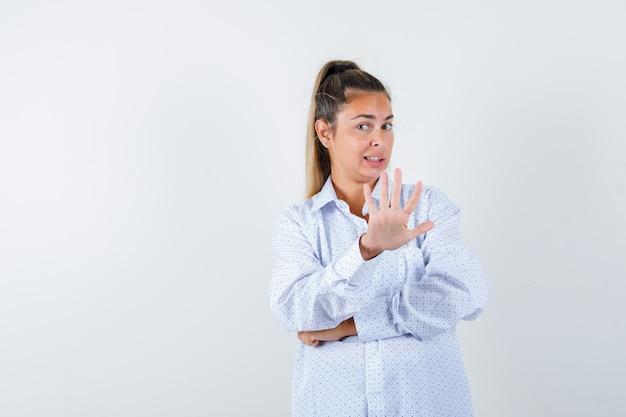 Молодая женщина показывает знак остановки в белой рубашке и выглядит взволнованно