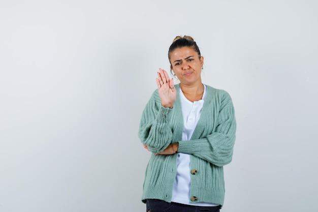 흰색 셔츠와 민트 그린 카디건에 정지 신호를 표시 하 고 해리 찾고 젊은 여자