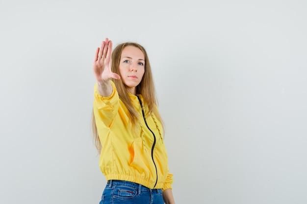 노란색 폭격기 재킷과 블루 진에 정지 신호를 표시하고 심각한, 전면보기를 찾고 젊은 여자.