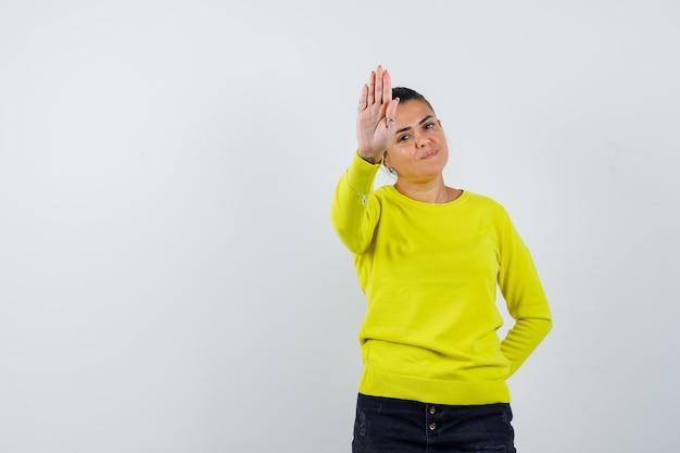 노란색 스웨터와 검은색 바지를 입고 정지 신호를 보내고 행복해 보이는 젊은 여성