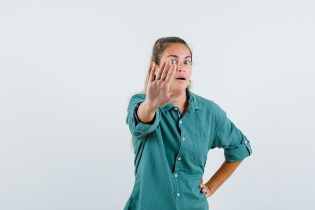 Young woman showing stop sign while holding one hand on waist in green blouse and looking serious