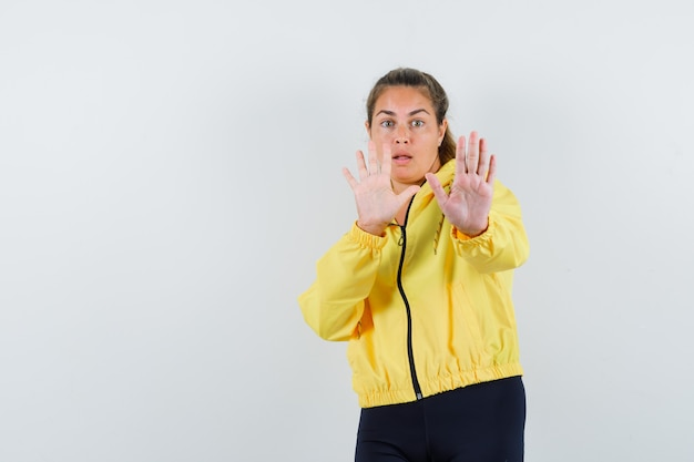 Young woman showing stop sign with both hands in yellow bomber jacket and black pants and looking scared