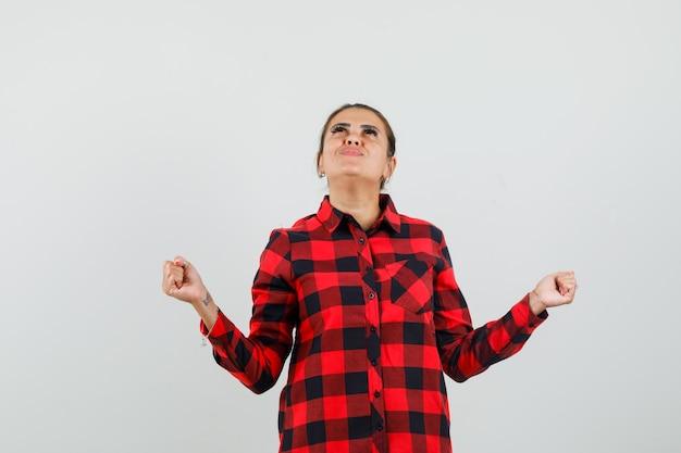 チェックシャツで成功ジェスチャーを示し、感謝の気持ちを表す若い女性、正面図。