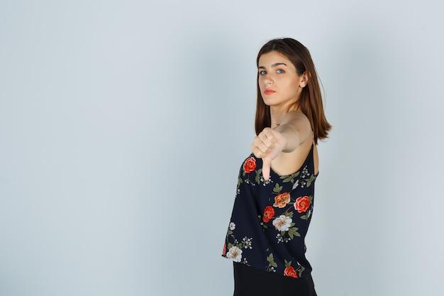 Giovane donna che mostra pollice in giù in camicetta, gonna e sembra dispiaciuta.