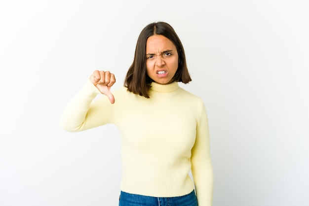 Young woman showing thumb down and expressing dislike
