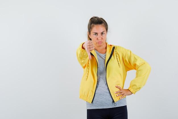 Giovane donna che mostra il pollice verso il basso in t-shirt, giacca e guardando dispiaciuto, vista frontale.