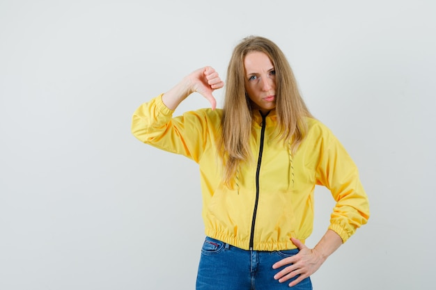 Young woman showing thumb down while holding hand on waist in yellow bomber jacket and blue jean and looking displeased , front view. Free Photo