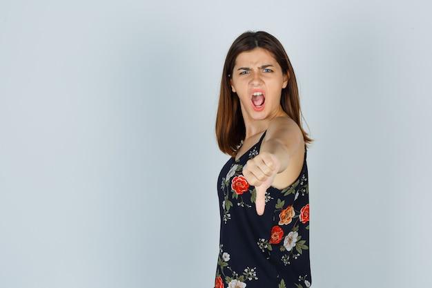 ブラウスで叫び、攻撃的に見える間、親指を下に見せている若い女性。
