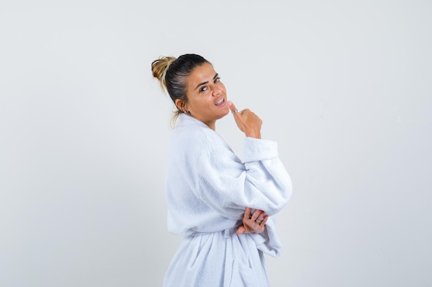 Young woman showing thumb up in bathrobe and looking confident