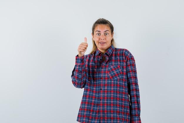 Giovane donna che mostra il pollice in su in camicia a quadri e sembra carina