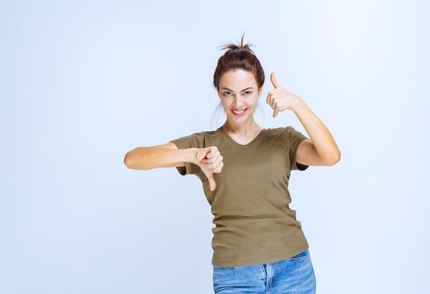 Giovane donna che mostra i segni del pollice su e giù