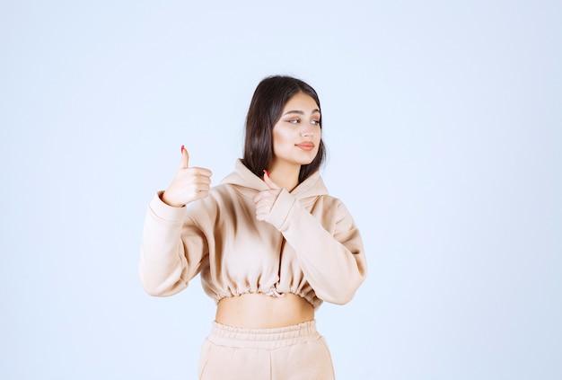 親指を立てる手サインを示す若い女性 無料写真